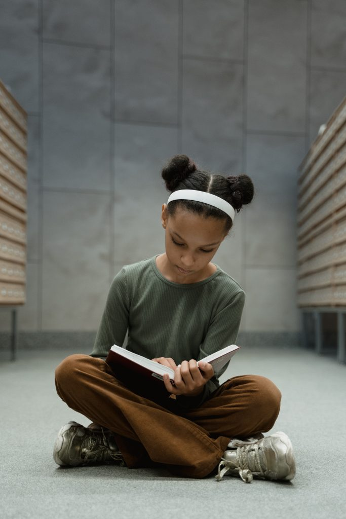 A young girl sitting cross legged on the floor and reading a book.
