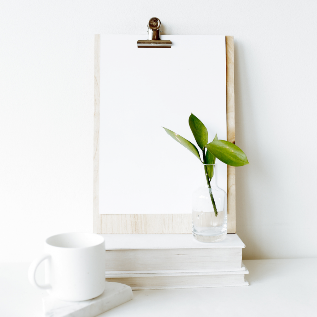 A chipboard with a white piece of paper on it standing up against a wall with a small plant and a cup of coffee in front of it.