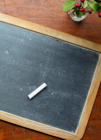 A blank chalkboard sitting on a wooden table with a piece of white chalk on it.