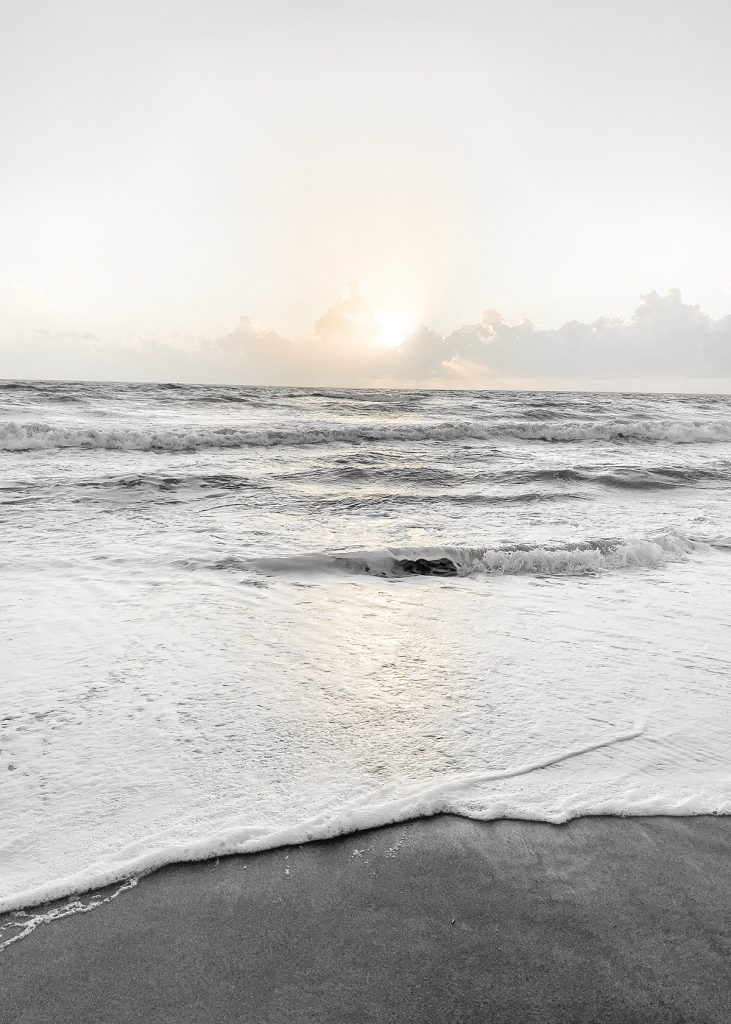 The sun coming up over the clouds with the tide lapping the sandy beach in the foreground