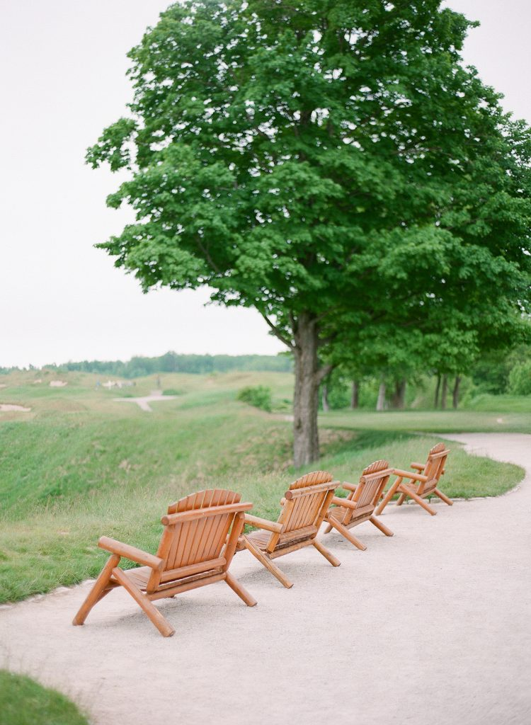 Wooden lawn chairs in a row overlooking gently rolling hills and a green field