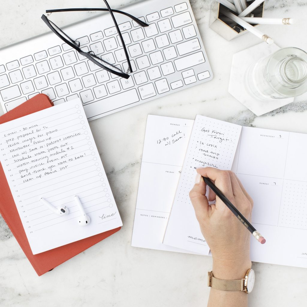 Notebooks, earbuds, and calendars scattered on a desk.