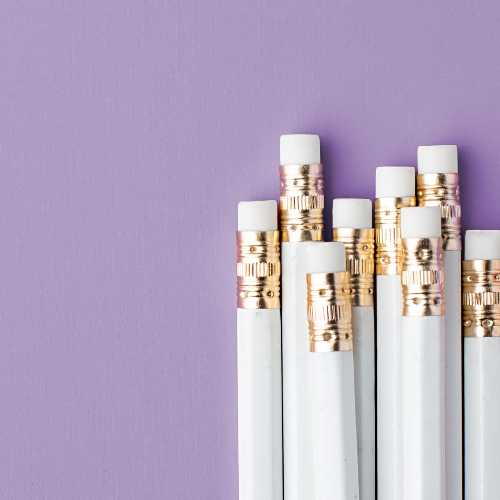 The end of a group of white pencils on a purple background.
