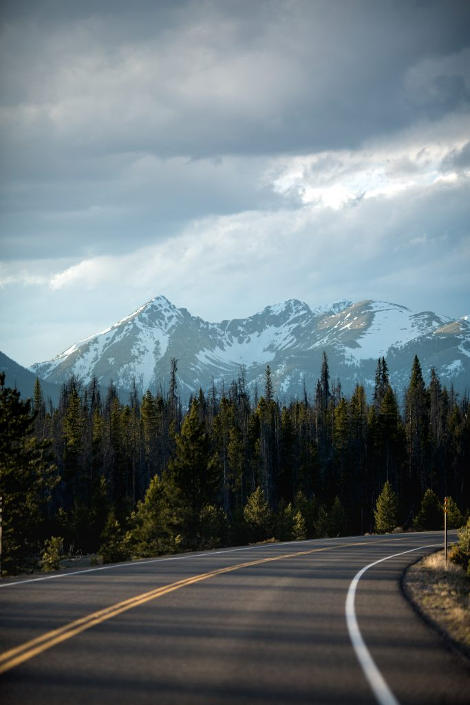 A paved road curving out of sight as you look at a snow-capped mountain.