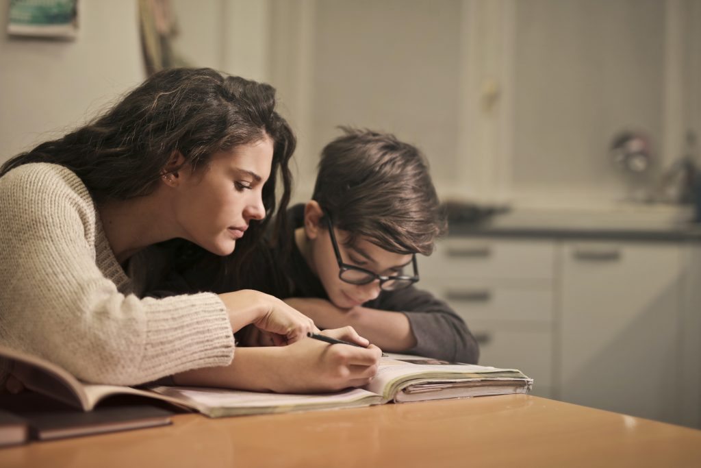 A mother and son bending over a book at the kitchen table working on their homeschool work.