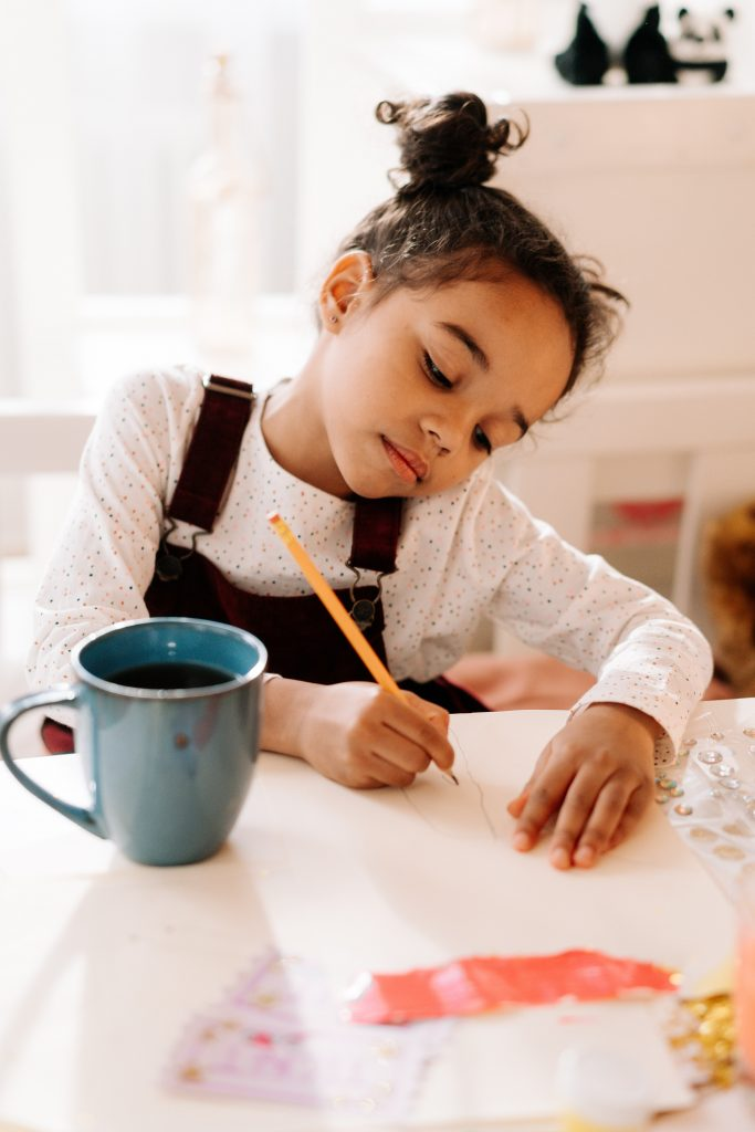 A young girl sitting at a table and working on her homeschooling project.