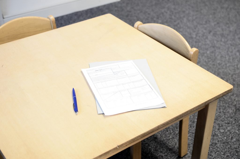 Worksheets and a pen sitting on a wooden desk with chairs around it.